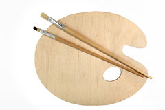 Una nuova, tavolozza classica e di legno dell'artista e due spazzole Isolato su priorità bassa bianca Vista da sopra Immagini Stock