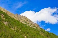 Una nuvola bianca sembra uscire dal lato di una montagna Immagine Stock Libera da Diritti