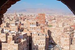 Una ojeada de casas y de palacios adornados detrás de la pared del arco en la ciudad vieja de Sana'a, Yemen Foto de archivo