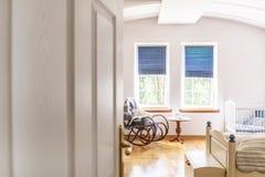 Una ojeada a través de una media puerta abierta en un dormitorio y un cuarto m del ` s del bebé foto de archivo