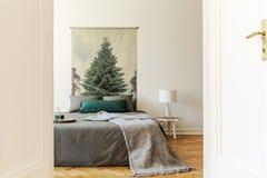 Una ojeada a través de una puerta abierta en un interior simple del dormitorio del estilo con una cama se vistió en las hojas gri foto de archivo libre de regalías