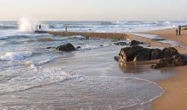 Una onda mojan a los pescadores que se rompe contra un embarcadero en la costa sur de KZN, Suráfrica Imagenes de archivo