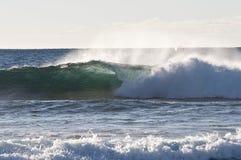 Una onda que causa un crash hacia línea de la playa Foto de archivo libre de regalías