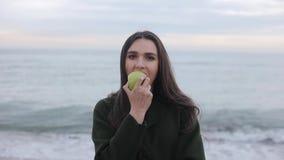 Una opinión cercana una muchacha atractiva hermosa que come una manzana fresca en la playa Una muchacha en una capa verde en la p almacen de metraje de vídeo