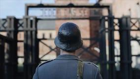 Una opinión cercana posterior un soldado alemán que se coloca delante de un campo de exterminación, dando vuelta alrededor, miran metrajes