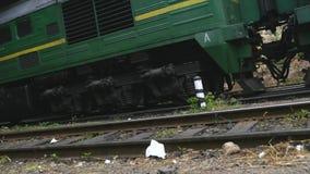 Una opinión de ángulo bajo de los coches de tren que pasan a lo largo de una opinión de ángulo bajo de la vía de la opinión de án almacen de video
