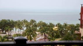 Una opinión de desplazamiento del foco de un hotel que mira hacia fuera sobre las palmeras y el océano durante una tormenta cerca metrajes