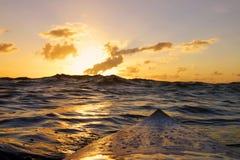 Una opinión de las personas que practica surf de una puesta del sol hermosa en el océano fotos de archivo libres de regalías