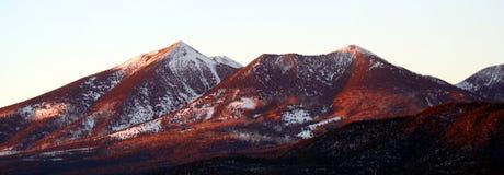 Una opinión del invierno de los picos en la puesta del sol Foto de archivo