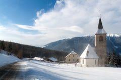 Una opinión del invierno de una pequeña iglesia con una aguja alta Imágenes de archivo libres de regalías