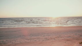 Una opinión del panorama de una puesta del sol rosada y azul hermosa en la orilla de mar almacen de metraje de vídeo