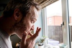 Una opinión del perfil un hombre que se lame los fingeres después de comer en foto de archivo