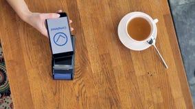 Una opinión desde arriba sobre una taza de café y un smartphone durante un pago de NFC metrajes