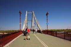 Una opinión el puente peatonal y la gente que da un paseo en él Foto de archivo libre de regalías