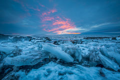 Una opinión sobre masas de hielo flotante de la toma panorámica, debajo de un cielo coloreado de la puesta del sol cerca de las c Imagen de archivo