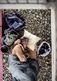 Una opinión superior el hombre sin hogar del mendigo que miente en el aire libre de tierra en ciudad, durmiendo imagen de archivo libre de regalías