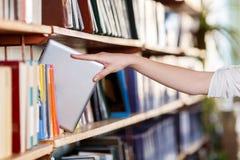 Una opinión superior sobre la mano femenina con el libro en biblioteca Imagen de archivo