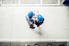 Una opinión superior un ingeniero industrial del hombre y de la mujer con el tablero en una fábrica fotos de archivo libres de regalías