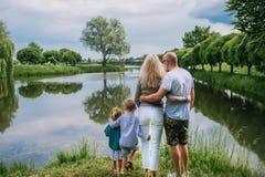 Una opinión trasera la familia con dos niños del niño al aire libre por el lago en verano foto de archivo libre de regalías