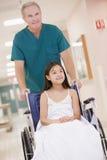 Una ordenanza que empuja a una niña en un sillón de ruedas Imagen de archivo