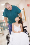 Una ordenanza que empuja a una niña en un sillón de ruedas Fotos de archivo
