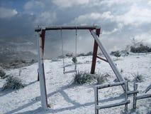Una oscilación cubierta con nieve Foto de archivo