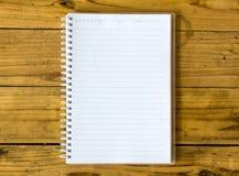 Una página en blanco del cuaderno en la opinión superior del cuaderno de madera de la oficina de la tabla para Foto de archivo