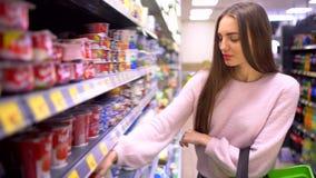 Una padrona femminile da solo cerca l'ingrediente di qualità di freschezza del latte nel mercato della città Grazioso sveglio att stock footage