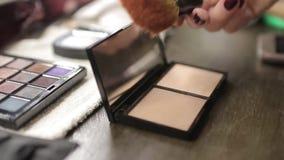 Una paleta con sombras de ojos y un cepillo del maquillaje: cosméticos del ` s de las mujeres Maquillaje de la mañana Cosméticos  almacen de video