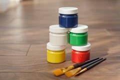 Una paleta multicolora de pinturas y de tres cepillos foto de archivo