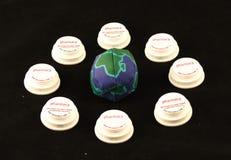 Una palla con il globo su ha circondato da otto coperchi della bottiglia di prescrizione su un fondo nero Immagini Stock