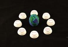 Una palla con il globo su ha circondato dai coperchi della bottiglia di prescrizione su un fondo nero Immagine Stock