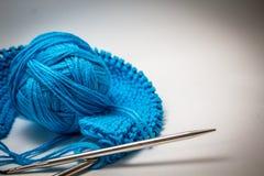 Una palla di filato blu su un fondo bianco con i ferri da maglia fotografie stock libere da diritti