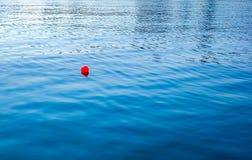 Una palla di galleggiamento rossa nel mare immagine stock