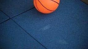 Una palla di pallacanestro salta sulle mattonelle di gomma, il Mo lento, gioco stock footage