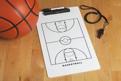 Una pallacanestro con la lavagna per appunti ed il fischio della vettura su un gymn di legno Fotografia Stock