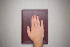 Una palma del hombre en un libro, un juramento en la biblia fotografía de archivo