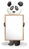 Una panda que lleva a cabo a un tablero vacío Imagenes de archivo