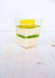 Una panna cotta di verde del dessert della frutta con il kiwi ed il maccherone sopra fondo bianco Fotografie Stock