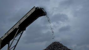 Una panoramica dei bei pezzi del carbone che cadono dal nastro trasportatore alla miniera di carbone video d archivio