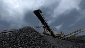 Una panoramica di un carbone che cade dal nastro trasportatore alla miniera di carbone video d archivio