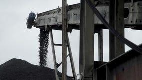 Una panoramica di un erogatore del carbone che forma un mucchio enorme di carbone archivi video
