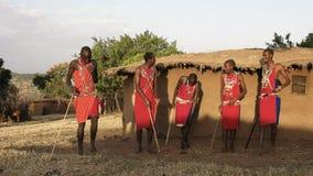 una panoramica 60p di cinque guerrieri di maasai che ballano ad un villaggio vicino ai masai Mara video d archivio