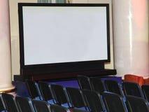 Una pantalla grande del plasma de la demostración y filas de los asientos para los espectadores Foto de archivo