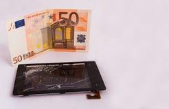 Una pantalla táctil quebrada con una exhibición y un billete de banco euro Aislado en el fondo blanco Fotos de archivo