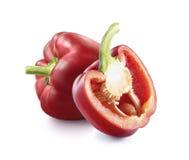 Una paprika y mitad rojos maduros aislados en blanco Imagen de archivo libre de regalías
