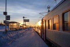 Una parada ferroviaria nevada con un tren y el levantamiento del sol Fotografía de archivo