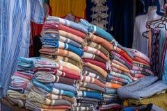 Una parada típica del mercado que vende una gama de ropa y de baratijas a los turistas en Marrakesh foto de archivo libre de regalías