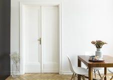 Una pared blanca con la puerta doble al lado de una mesa de desayuno de madera y sillas en un interior del comedor Foto verdadera fotos de archivo
