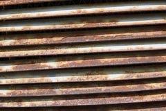 Una pared de ladrillo con una parrilla oxidada del hierro fotos de archivo